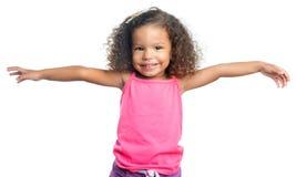 有一种非洲的发型的快乐的小女孩笑与她的胳膊的延伸了 图库摄影