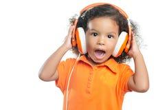 有一种非洲的发型的激动的小女孩享受她的在明亮的橙色耳机的音乐 库存图片