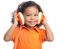 有一种非洲的发型的Lttle女孩享受她的在明亮的橙色耳机的音乐 免版税库存照片
