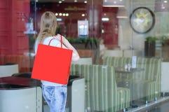 有一红色购物带来的女孩在玻璃咖啡馆陈列室附近站立 免版税图库摄影