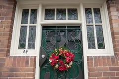 有一绿色门和视窗的红砖墙壁 库存照片