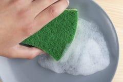 有一绿色spunge的一只手洗涤有洗涤剂泡沫的一块灰色陶瓷板材 免版税库存照片