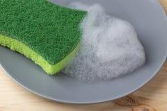 有一绿色spunge的一只手洗涤有洗涤剂泡沫的一块灰色陶瓷板材 库存照片