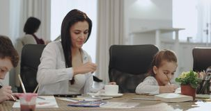 有一美好三儿童工作的俏丽的成熟母亲网上,当做与她的孩子的家庭作业在厨房时 股票视频