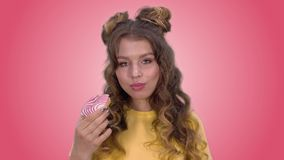 有一美好称呼的可爱的女孩吃一个多福饼并且享受口味 股票视频