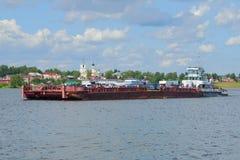 有一艘驳船的拖轮Rechnoy-76以市为背景的中央部分梅什金 免版税库存图片