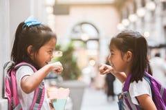 有一起使用在学校以后的书包的两个逗人喜爱的亚裔儿童女孩在学校 库存图片