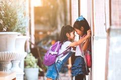 有一起使用在学校以后的书包的两个逗人喜爱的亚裔儿童女孩在学校 免版税库存图片
