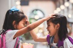 有一起使用在学校以后的书包的两个逗人喜爱的亚裔儿童女孩在学校 免版税库存照片