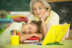 有一起做家庭作业的小女孩的祖母 免版税库存图片