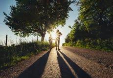 有一起儿子步行的父亲在日落路 库存照片