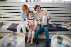 有一起坐和看照相机的两个孩子的愉快的家庭 库存照片