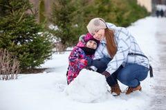 有一起坐在雪的女儿的愉快的母亲在冬天公园 免版税库存照片