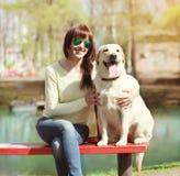 有一起坐拉布拉多猎犬的狗的所有者妇女 免版税库存图片