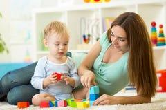 有一起她的儿子儿童游戏的妈妈 免版税图库摄影