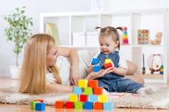有一起她的儿童游戏的年轻妈妈 免版税库存图片