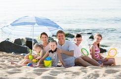 有一起孩子的活跃家庭在海滩开会 免版税图库摄影