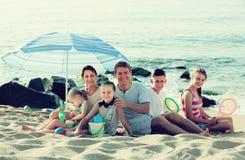 有一起孩子的活跃家庭在海滩开会 库存照片