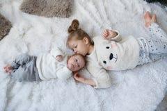 有一起放松在一张白色床上的一个新出生的小兄弟的逗人喜爱的女孩 库存照片