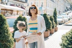 有一起旅行小的女儿的母亲调查城市的地图和 图库摄影