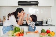 有一起烹调她的女儿的母亲在厨房里 免版税库存图片