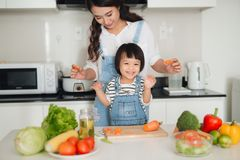 有一起烹调她的女儿的母亲在厨房里 免版税图库摄影