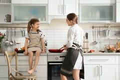有一起烹调逗人喜爱的小女孩的年轻保姆 库存图片