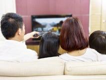 有一起看电视的两个孩子的亚洲家庭 免版税图库摄影