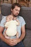 有一起睡觉在沙发的小儿子的疲乏的父亲 免版税库存照片