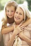 有一起笑在沙发的孙女的祖母 免版税库存照片