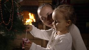 有一起装饰圣诞树的小逗人喜爱的女儿的年轻母亲 股票录像