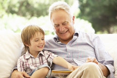 有一起读在沙发的孙子的祖父 库存图片