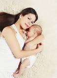 有一起说谎睡觉的婴孩的可爱的年轻母亲 库存照片