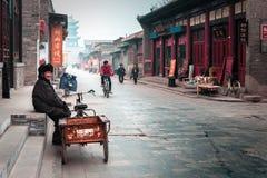 有一辆三轮车的老人在平遥,中国街道  免版税库存照片