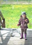 有一辆卡车的小女孩在木房子大阳台在乡下用在背景的蒲公英 免版税库存图片