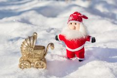 有一辆婴儿推车的圣诞老人在雪 我首先的圣诞节 库存图片