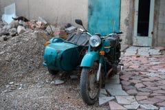 有一辆婴儿推车的老苏联摩托车在转储 库存图片