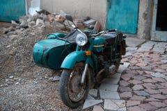 有一辆婴儿推车的老苏联摩托车在转储 免版税库存图片