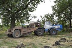 有一辆平地机的一台大拖拉机在拖车 种植播种机弹簧的农业机械 库存照片