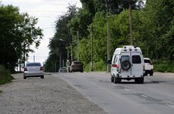 有一辆救护车的闪光灯的汽车在乘驾的镇在路 免版税图库摄影