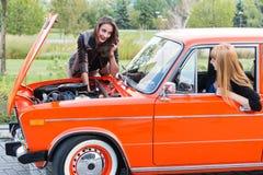 有一辆残破的汽车的两个女孩 免版税库存图片