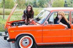 有一辆残破的汽车的两个女孩 库存照片