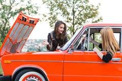 有一辆残破的汽车的两个女孩 图库摄影