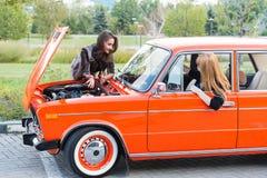 有一辆残破的汽车的两个女孩 免版税图库摄影