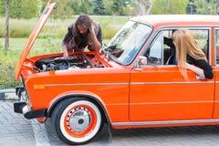 有一辆残破的汽车的两个女孩 免版税库存照片
