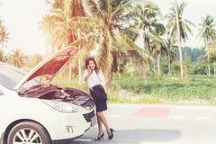 有一辆残破的汽车的企业亚裔妇女要求协助 免版税库存图片