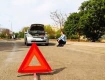 有一辆残破的汽车的一名妇女,她等待协助,在midd 库存照片