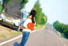 有一辆残破的汽车的女孩 库存照片