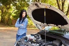 有一辆残破的汽车的恼怒的妇女 免版税库存照片
