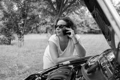 有一辆残破的汽车的年轻可爱的女孩 库存照片